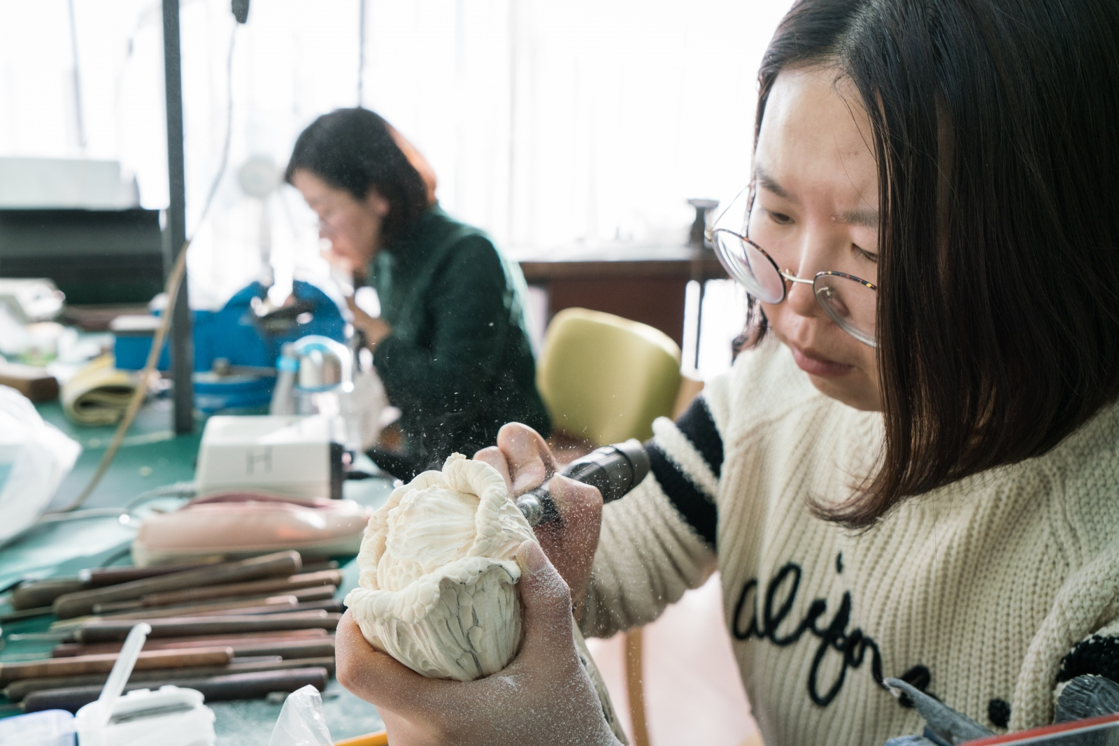 He Na, 27, works on an ivory statue at her workstation at Li Chunke's ivory carving workshop in Beijing, China on December 10, 2017.
