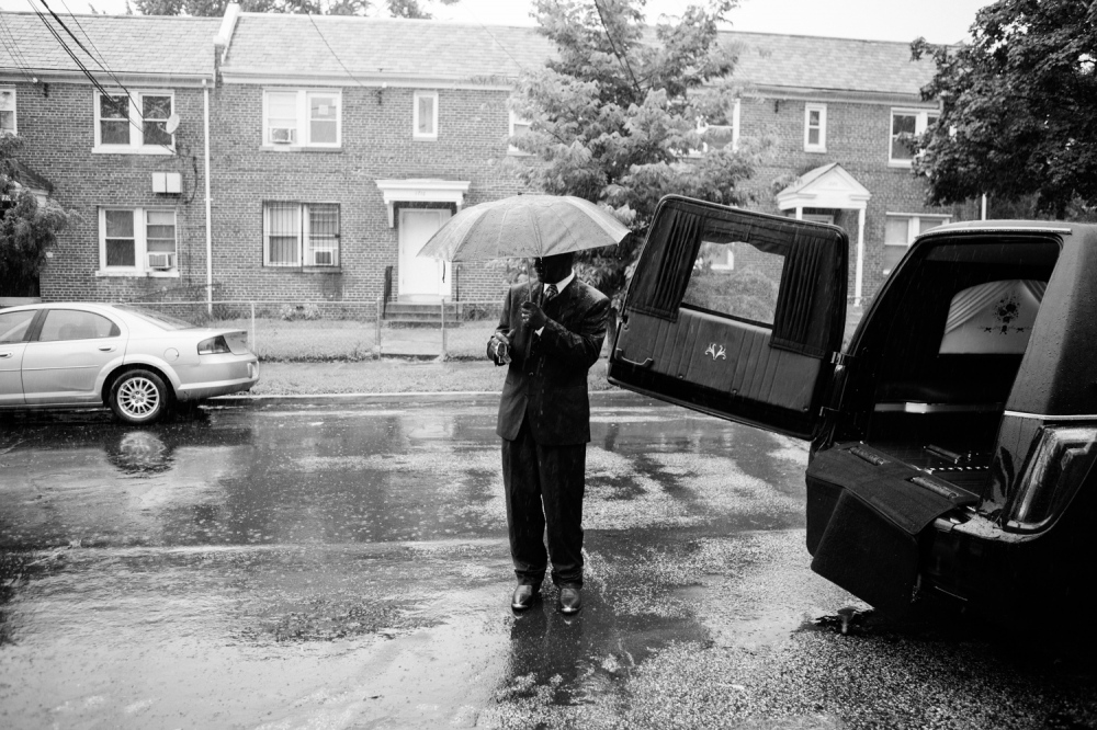 "A man waits in the rain during Milton Joseph Taylor's funeral July 28, 2017. Taylor, known as ""Skip King,"" ""Frog Eyes,"" and ""Froggy Eyes"" was born in December 5, 1959 in Washington, D.C. He passed away in July 13, 2017 and was a Barry Farm resident. ""He gave ten years back to me,"" says former Barry Farm resident Charles. Taylor represented incarcerated people and was a well-known leader and friend in the Barry Farm community."