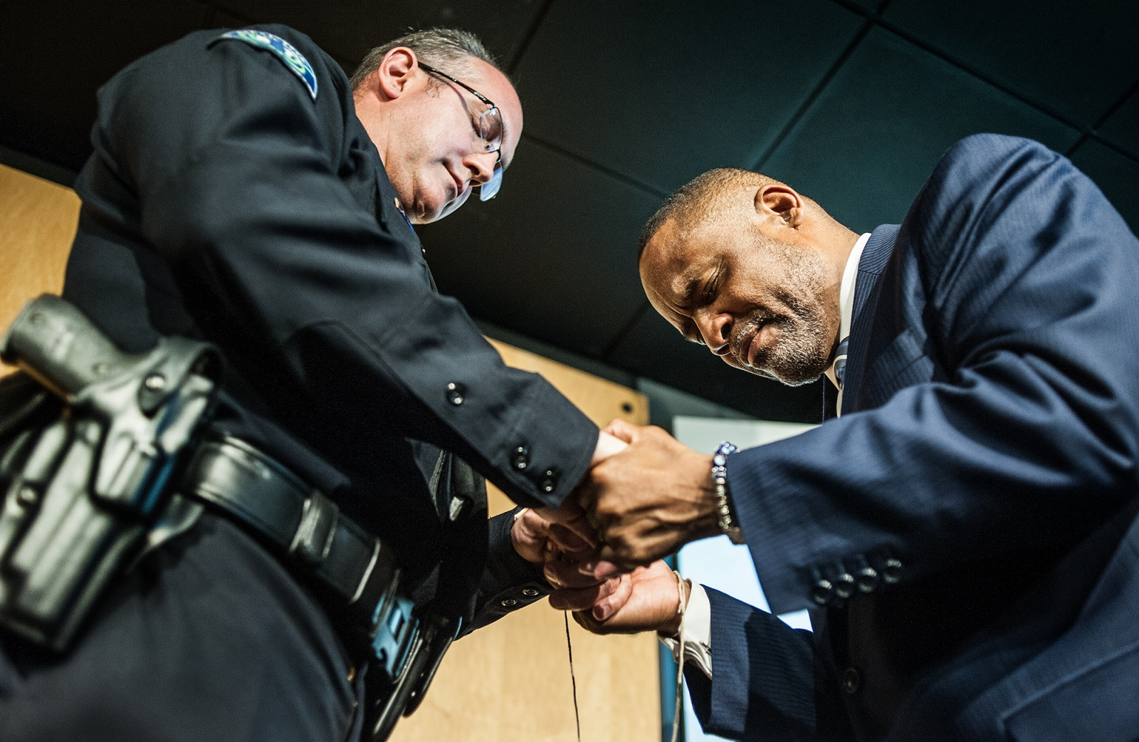 "Irvine Police Chief Mike Hamel bows his head in prayer with Pastor Mark Whitlock of Christ Our Redeemer AME Church after tying a thread around each others wrists as a symbol of unity during a ""thread ceremony."" The ceremony has held in the aftermath of an attack in Dallas that killed five police officers and multiple black men killed across the country by police."