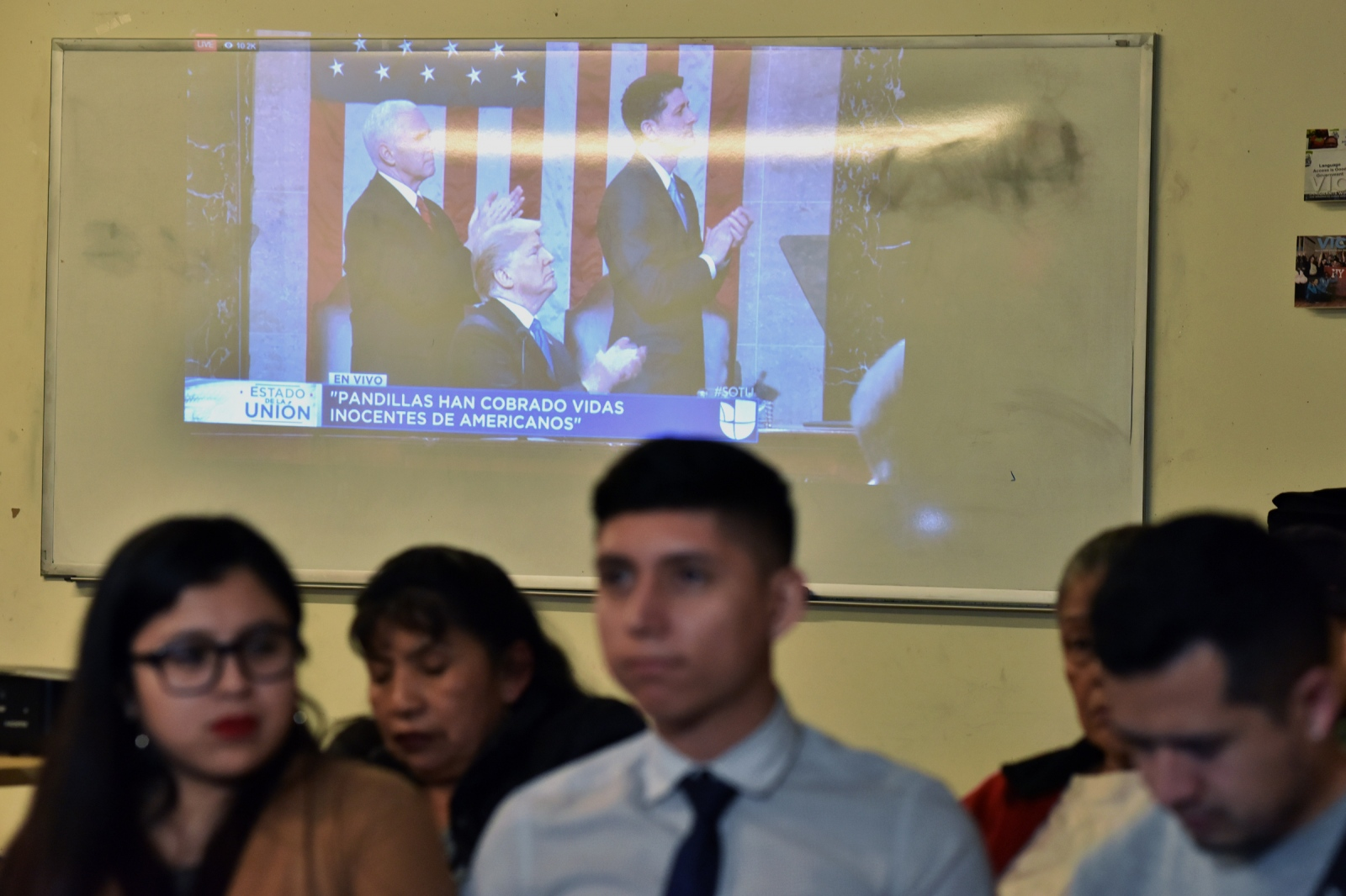 DACA recipients and Dreamers Yatziri Tovar,25 student of Political Sciences at City College and Anthony Alarcon student of Studies Film turn theirs backs on U.S President Donald Trump on screen during the State of Union speech at the pro-immigrant headquarters 'Make The Road New York' in Jackson Heights, Queens,on January 30, 2018 in New York City.