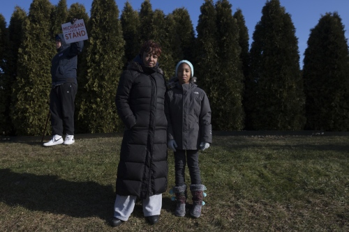 Stephanie Thornton, left, holds her daughter Kamari Thornton, 9, while Sen. Bernie Sanders speaks during a rally to stand up to Republicans and save healthcare on Sunday, Jan. 15, 2017 in Warren, Mich.