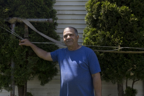 Gholam Nezhad pauses his yard work for a portrait outside his home on Monday, May 22, 2017 in Southwest Detroit, Mich.