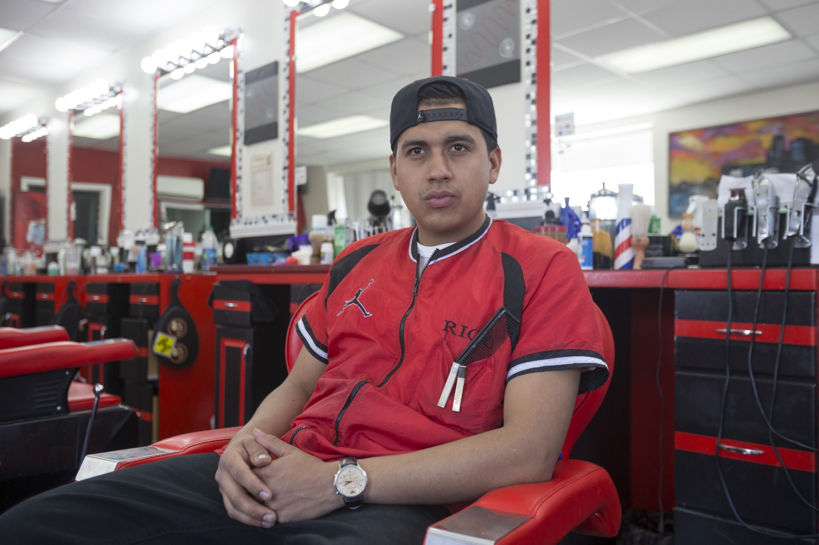 Southwest Styles barber, Ricardo Alvarez of Southwest Detroit, poses for a portrait in his chair at the shop in Detroit, Mich.