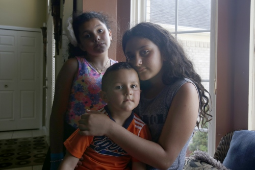 Siblings from clockwise, Meryana Butris, 9, Lilly Butris, 12, and Eli Butris, 3, at their home on Monday, June 12, 2017 in Sterling Heights, Mich. Their father Joe Butris was picked up by ICE and detained on Sunday, June 11, 2017.