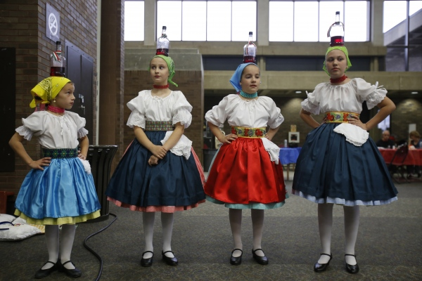 While balancing a glass jug on her head, Doda Simon, left, looks up at the older girls, Eva Fazes, Dorothy Sidau, and Anna Hussey all members of Kis Szivek or Little Hearts, a Hungarian dance ensemble, as they wait off stage before their performance at the 90th annual International Festival in Southfield.