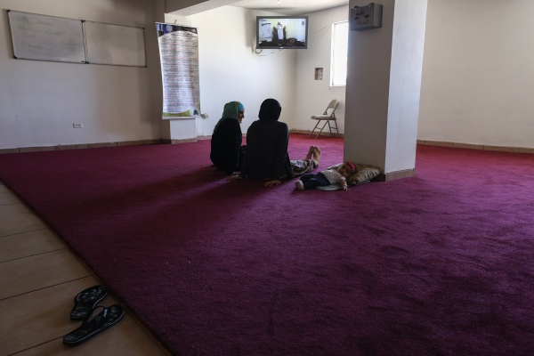Vanessa, left, Iman, and her baby watch in a separate room and through a television as an Imam from their mosque gives a lecture during a prayer session in Playas de Tijuana, Mexico, along the Mexico-U.S. border. A growing number of Muslims in the Tijuana area has prompted the building of more mosques.