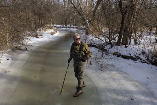Carl Clark, 64, of Farmington Hills, walks along the frozen Rouge River looking for a way to break through the ice to search for stoneflies at Heritage Park in Farmington Hills, Mich.