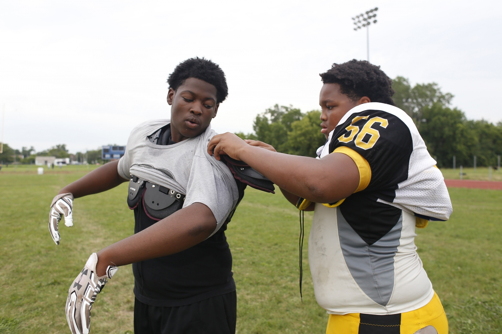 "Kaleb Hardy, 14, left, gets help putting his practice jersey over his new shoulder pads, from teammate Spencer Wallace, 14, during Camp Greatness in Detroit, Mich. Offensive tackle for the Los Angeles Chargers and Detroit native, Joe Barksdale, helped donate money, school supplies and football gear to students and athletes around Detroit. ""Detroit is a city full of resiliency and hard work, and that's what I carry with me now...I have to give back to the city that raised me,"" said Barksdale."