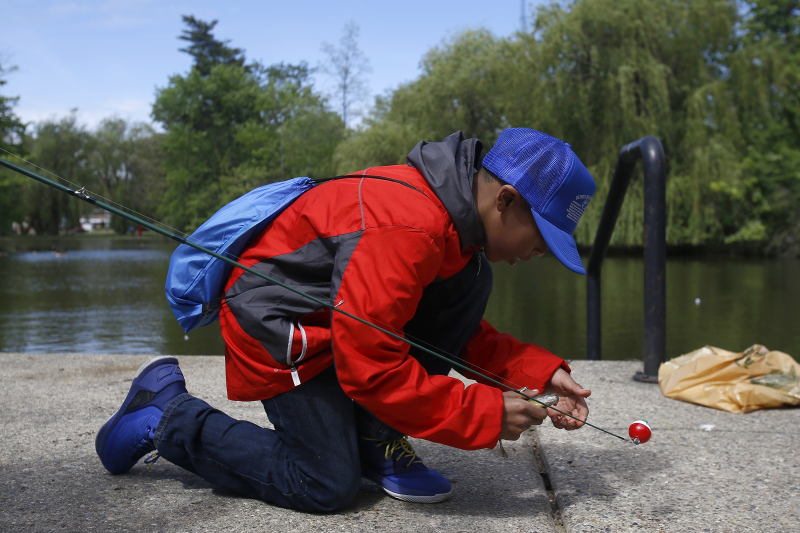 A young boy works hard to unhook a squirming fish he caught during the 21st annual Detroit Area Kids Fishing Derby in Palmer Park in Detroit, Mich.