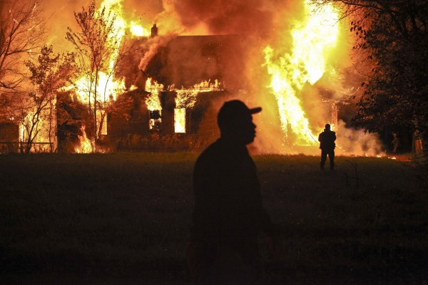 A man walks past an abandoned home completely engulfed in flames on Detroit's Eastside.