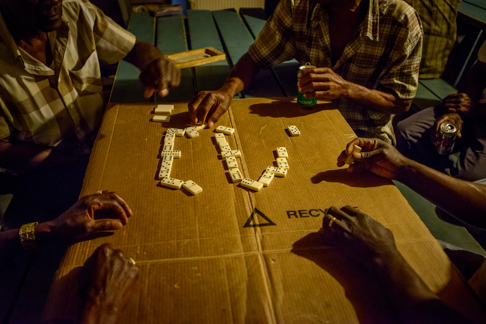 Jamaican Apple Pickers play a game of dominoes in the bunkhouse at Sunrise Orchards. Each play is 'announced' by slamming down a game piece.