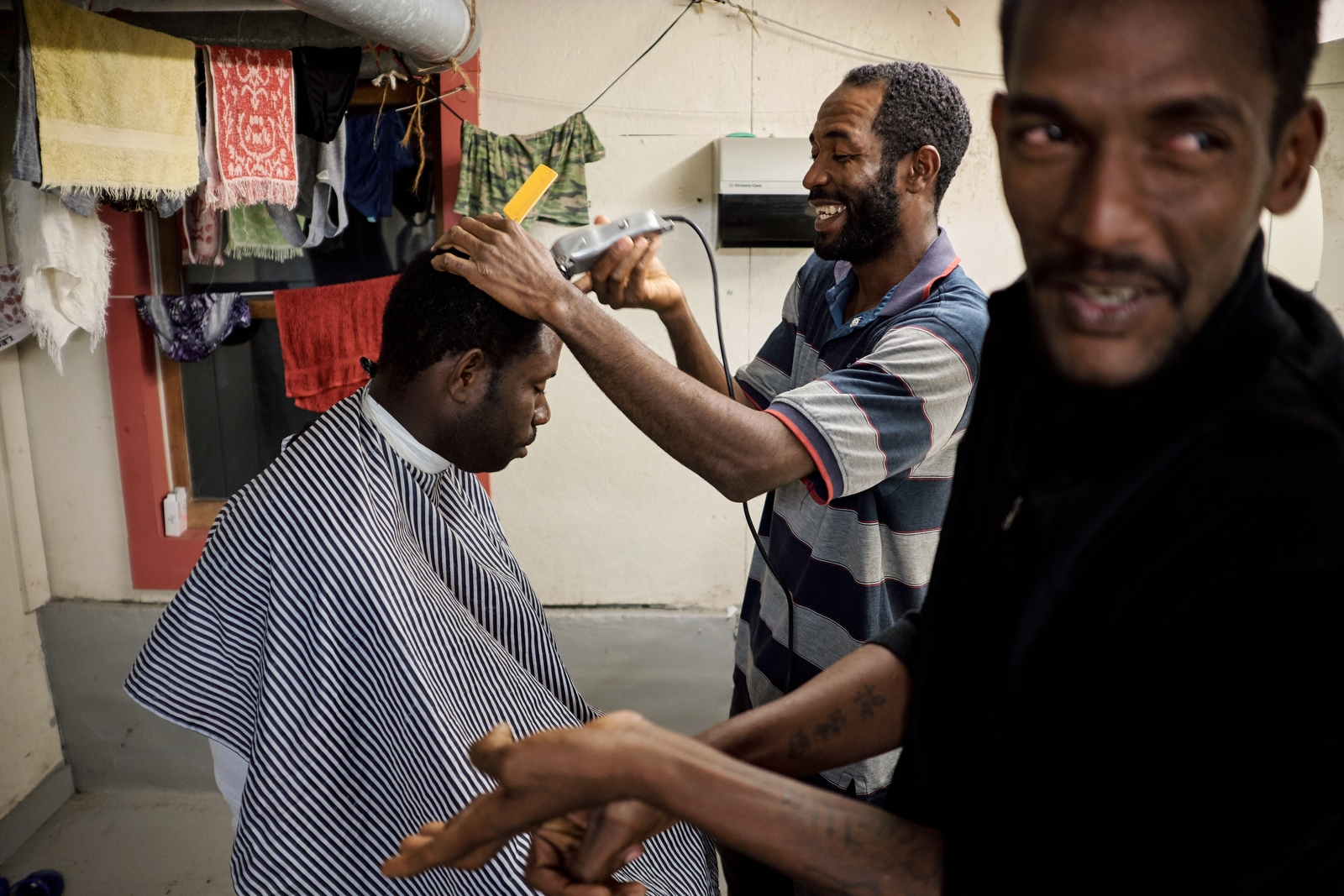 Carlington Senior, a professional barber back in Jamaica, gives hair cuts to his coworkers in the bunkhouse bathroom at Sunrise Orchards, Cornwall, Vermont.