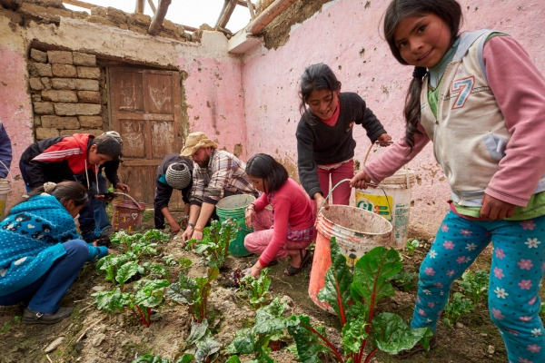 Aaron Ebner helps a group of schoolchildren spread compost on garden inside a greenhouse made from an abandoned school building in Chocquecancha, Lares Valley, Peru.