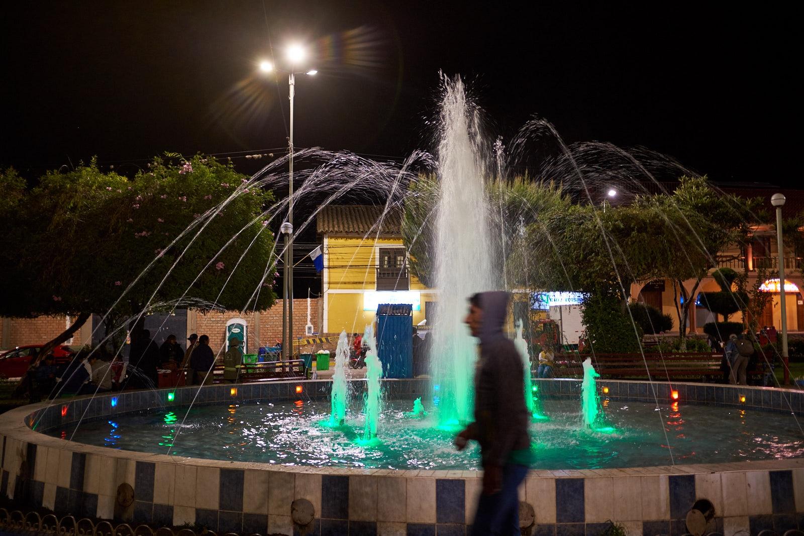 Man and fountain, Plaza de Armas, Calca, Peru.