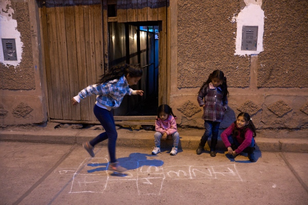 Young girls playing hopscotch in the street, Calca, Peru.