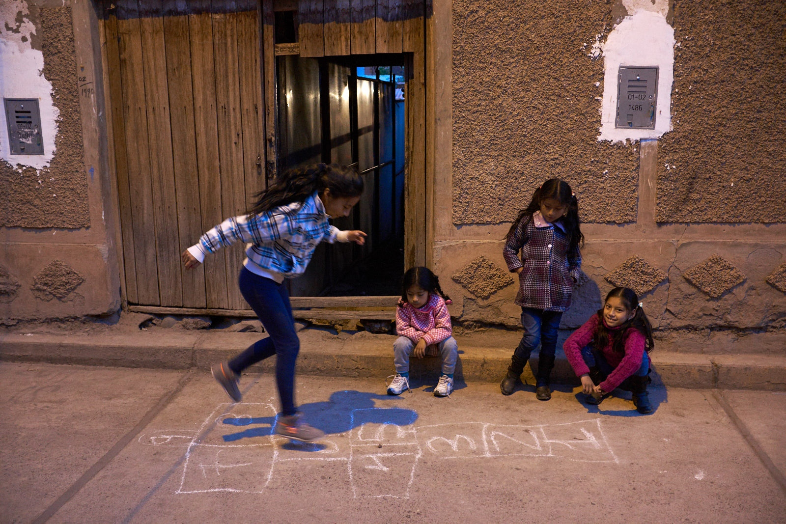 Young girls playing hopscotch in the street, Calca, Peru.