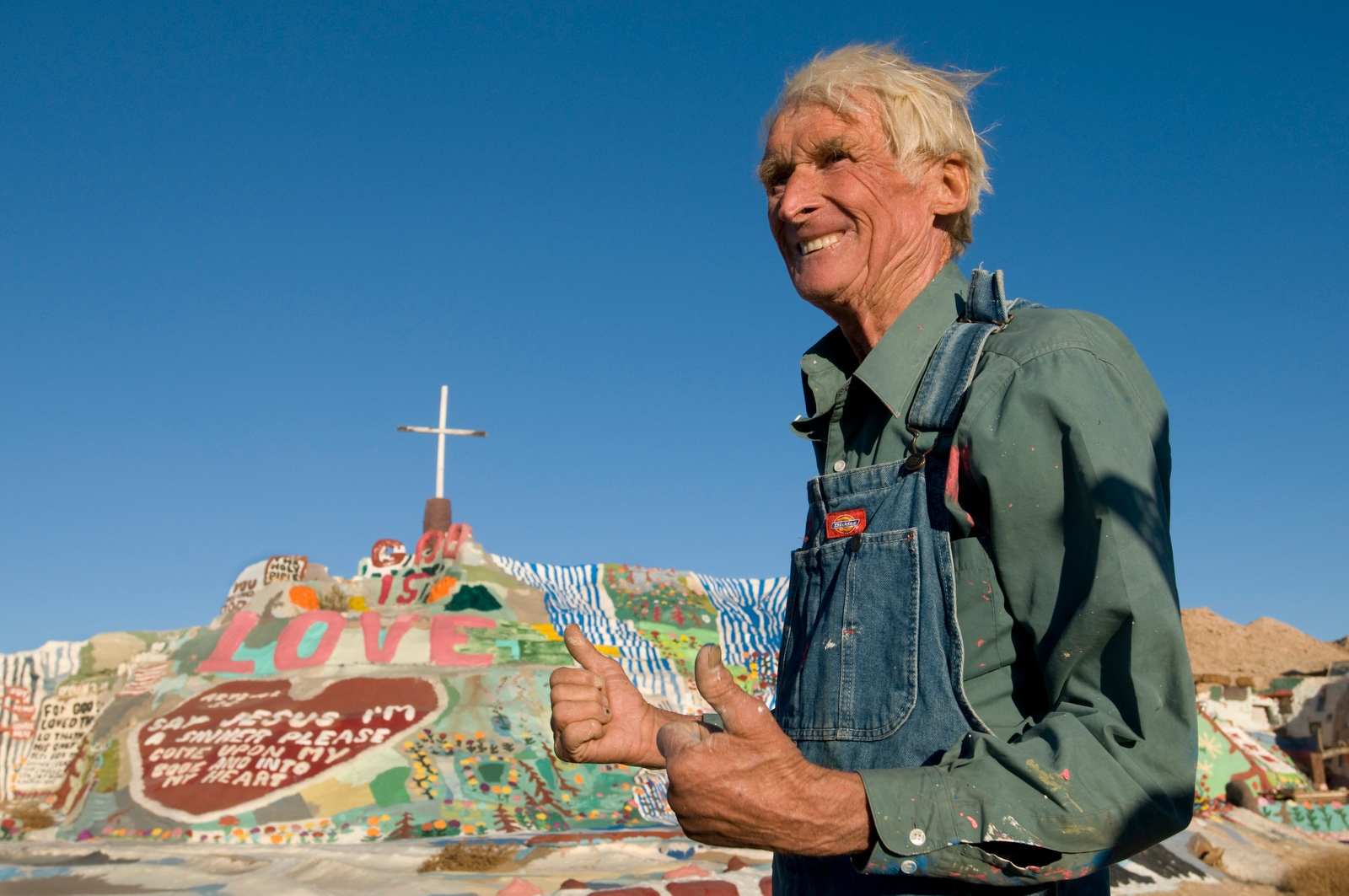 "Folk artist Leonard Knight in front of his adobe clay, straw, and house paint sculpture ""Salvation Mountain"" near the entrance to Slab City, Niland, California"