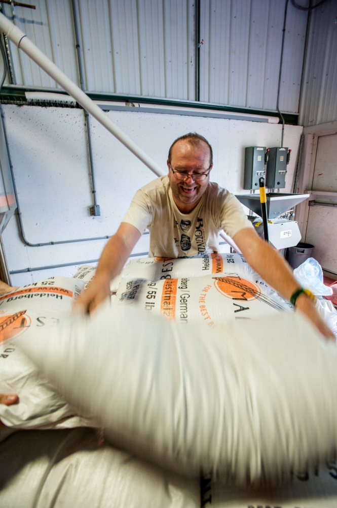 Steve Parkes unloads bags of ingredients in preparation for a day of brewing beer at the Drop-In Brewing Company, Middlebury, Vermont.