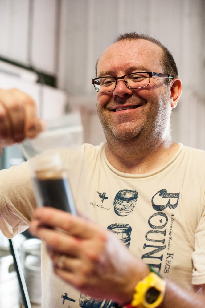 Steve Parkes of the Drop-In Brewing Company tests a sample from a fresh batch of beer wort, Middlebury, Vermont.