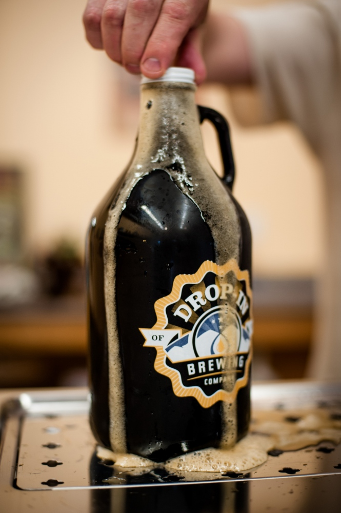 "Steve Parkes puts the cap on a freshly poured ""growler"" bottle of beer at the Drop-In Brewing Company's tasting room, Middlebury, Vermont."