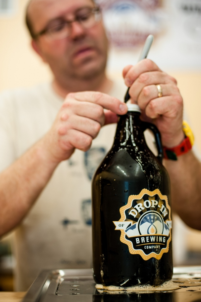 "Steve Parkes puts the cap on a freshly poured ""growler"" bottle of beer at the DropIin Brewing Company's tasting room, Middlebury, Vermont."