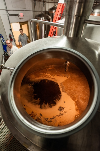 Steve Parkes and assistant Rock Hadsall enter the brewing room to check on progress of a fresh batch brewing in the foreground at the Drop-In Brewing Company, Middlebury, Vermont.