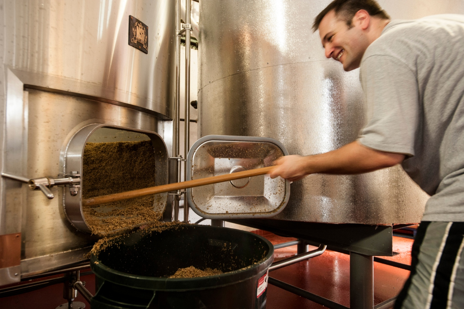 Assistant Rick Hadsall cleans out the leftover ingredients from the bottom of a brewing tank at the Drop-In Brewing Company, Middlebury, Vermont.