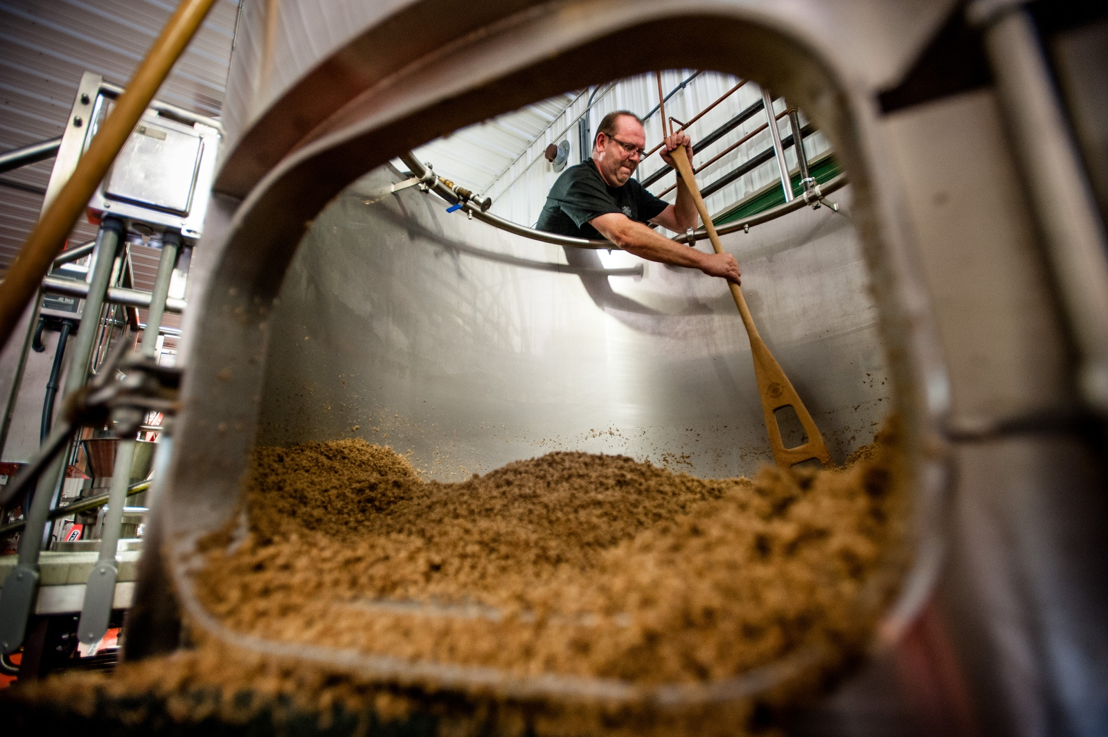 Steve Parkes cleans out the leftover ingredients from the bottom of a brewing tank at the Drop-In Brewing Company, Middlebury, Vermont.
