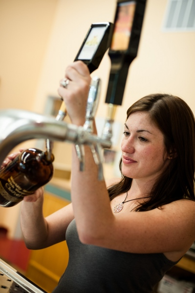 "Kaella Ryan, manager of the Drop-In Brewery tasting room, fills a ""squealer"" bottle with draft beer for a customer."