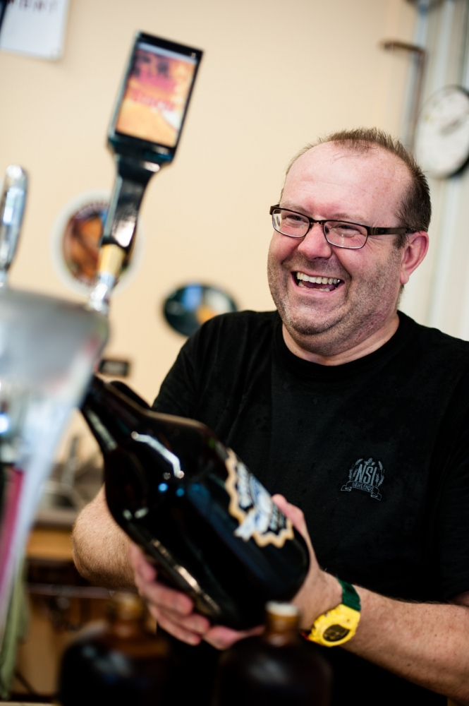 "Steve Parkes fills a ""growler"" bottle full of draft beer for a customer in the tasting room of the Drop-In Brewing Company, Middlebury, Vermont."