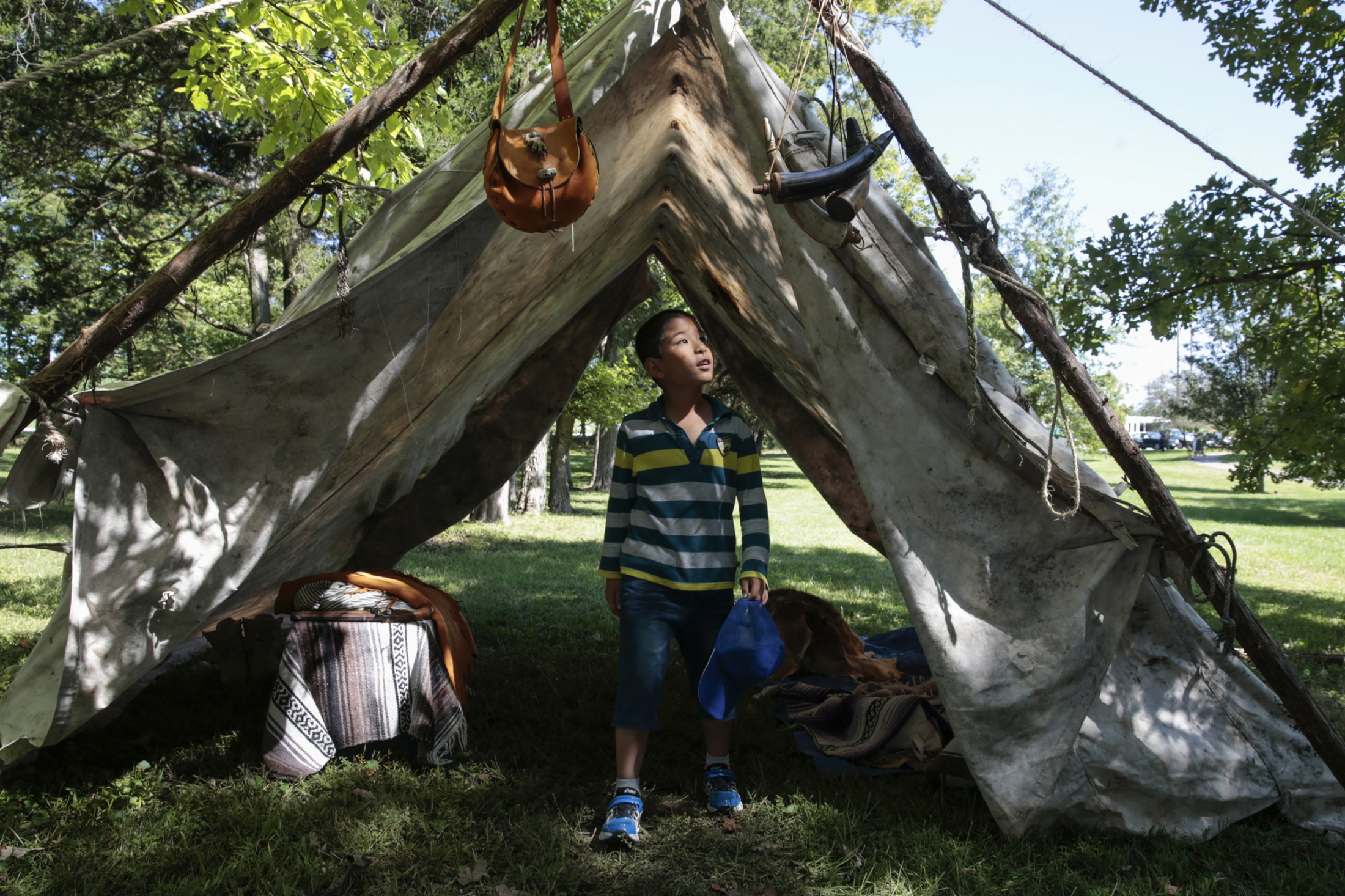 "Lucas He, 8, explores a 19th-century-style mountain man camp during Columbia's 39th annual Heritage Festival and Craft Show at Nifong Park. A dozen artisans and tradesmen dressed in 19th century attire, demonstrated their trades and sold their wares. Xiao Ling Guo, the boy's mother, said, ""We are newcomers, so I think it's really important for us to understand the depth of local culture."""