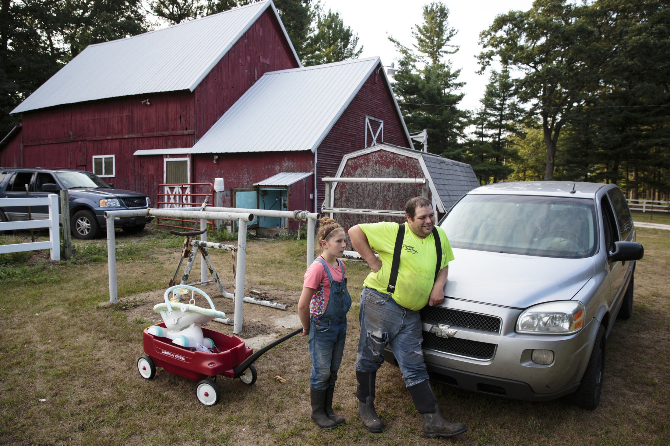 "Chad Bartlett and his daughter Mackenzie Maka, 10, chat with their neighbors at their hundred-year-old barn next to Chad's house in Twin Lake, Michigan. Chad left behind the city life to create an environment for his children to learn skills and lessons beyond the life of an urban city. ""We lived in an apartment for a long time,"" Chad said. ""Back then, we had to go out to do things, because they really couldn't go outside and play because there's no area that was ours. Here, it gets our family active a lot more, because we're outside doing stuff. We're not in the house all the time."""