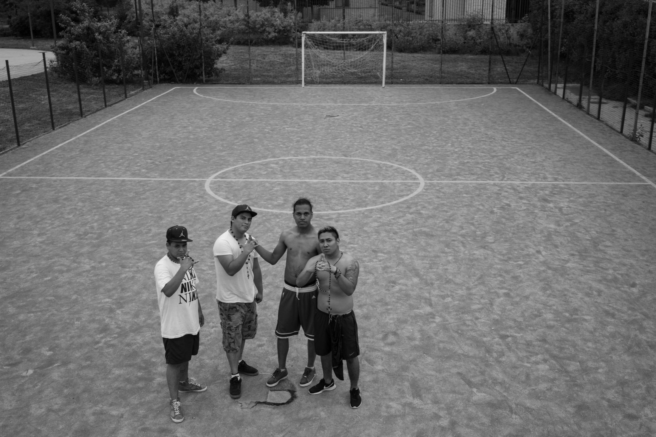 (from left to right) Erick, Milton, Sombra, and Crash pose for a photo at the soccer court where they play soccer. the Tribe in Milano plays soccer every week during summer to help them maintain a team attitude at all times.