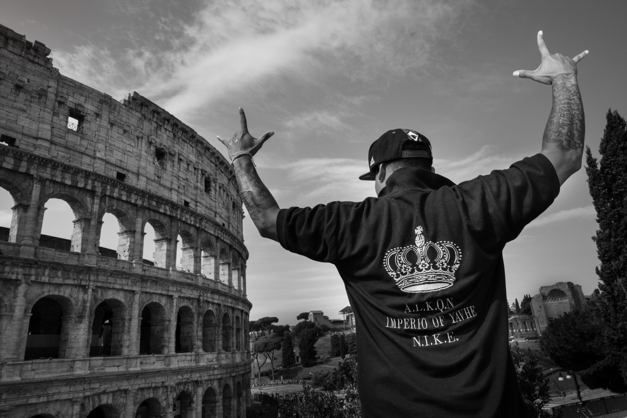 King Caos lifts his hands doing a 3 point crown sign beside the Roman Colosseum during a meeting of the Italian Latin Kings in Rome.