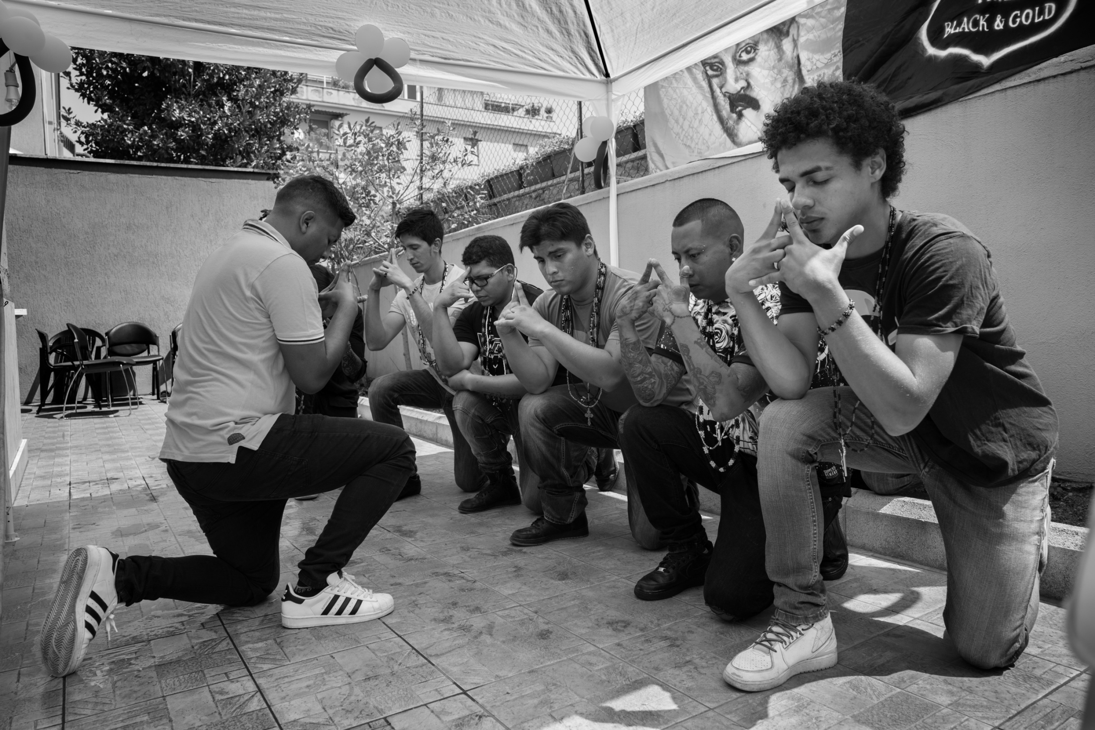 Latin Kings members pray on their knees during an important meeting in Rome. some of the topics discussed include teaching respect and love for gang members as well as telling them to study their literature and follow the steps that can lead them to be not only successful leaders within the gang but also outside of it as humans in society.