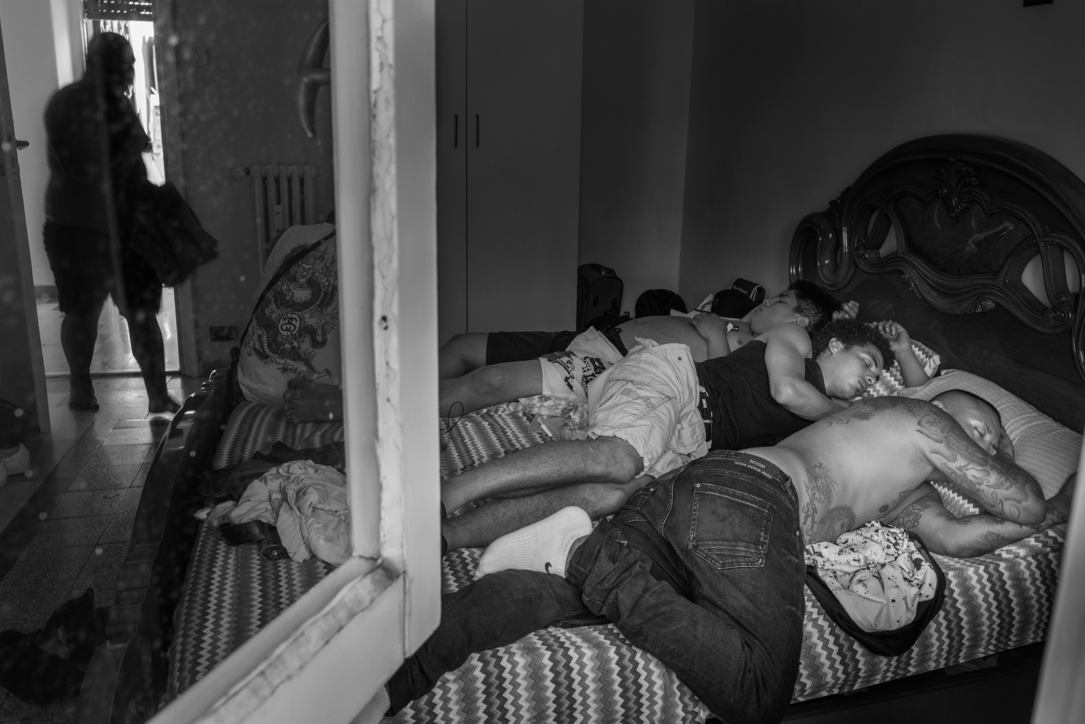3 members of the Latin Kings gang sleep on the same bed after a long night partying and celebrating a successful meeting.