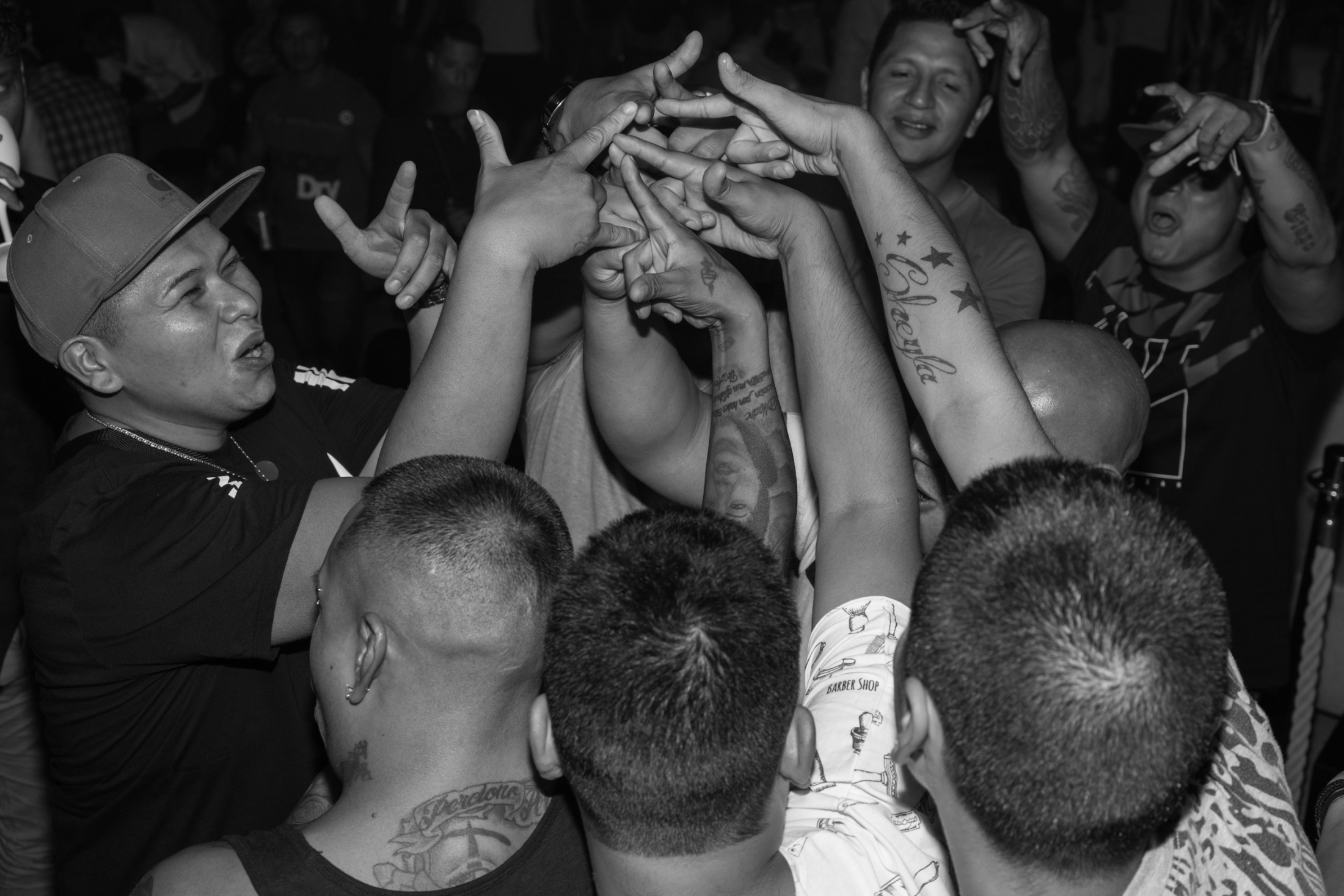 members of the Latin Kings gang form a circle and join their hands with 3 point crown signs at a local latin club in Milano.