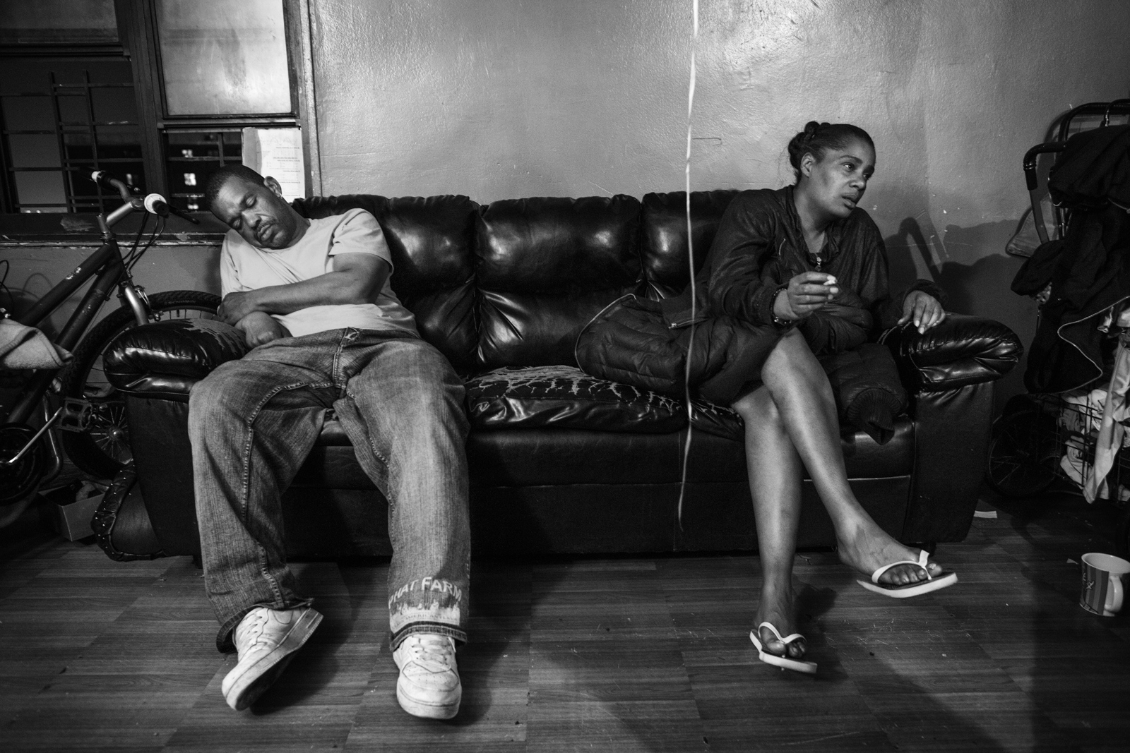 Relatives of Smokey on a couch after a birthday party celebration inside his apartment, the family environment is one of the main reasons why kids join gangs at an early age, trying to find someone who will support them and understand them.