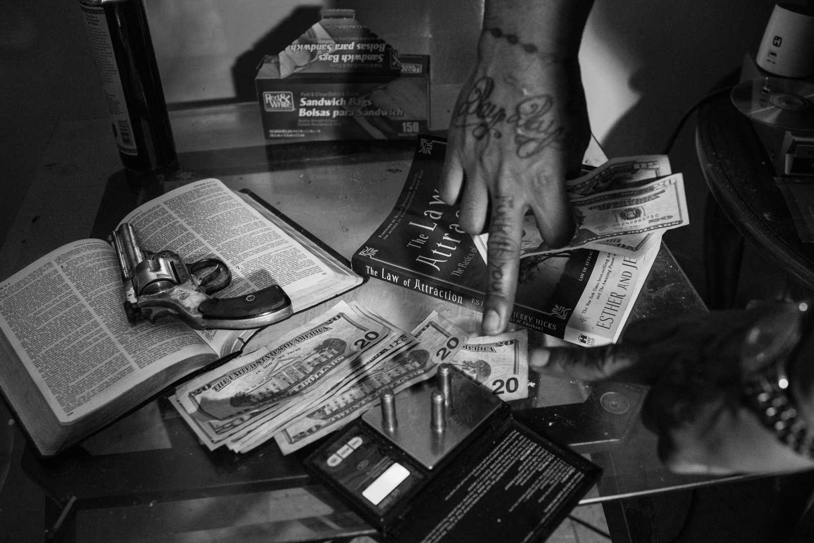 Teflon shows the table where he has displayed a gun laying on top of a Bible, several bullets, a balance for drugs and a book of the law of attraction, drug dealing and violence are part of the daily lives of gang members in New York.