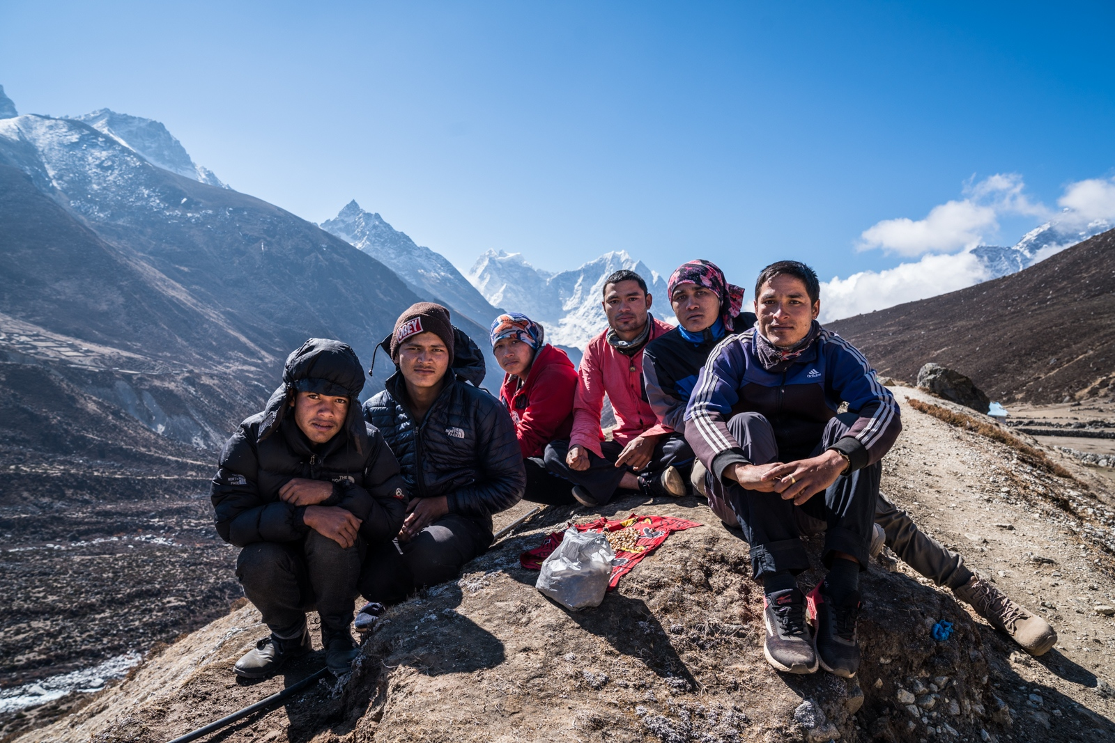 Nepali porters carrying a load for Indian tourists take a break on an old glacial moraine at around 5000m above sea level.