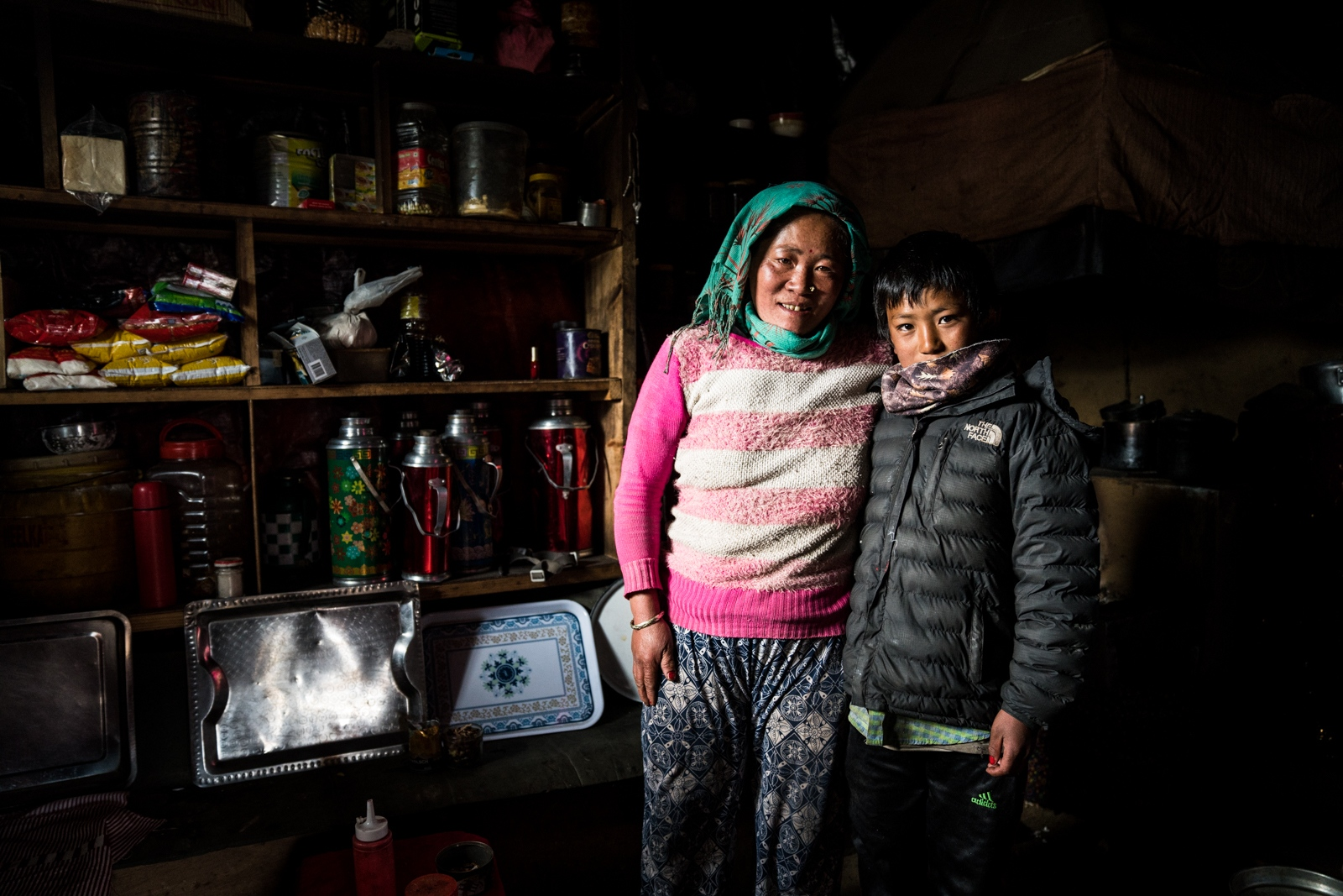 A mother and son inside their kitchen in the village of Thore.