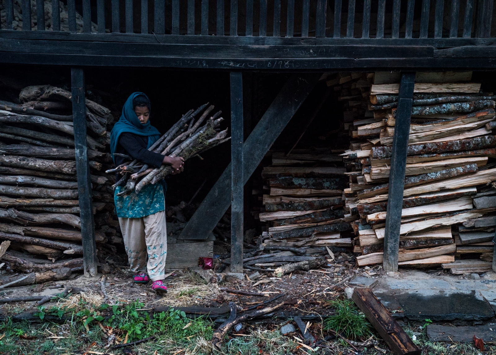 A woman carries firewood from a storage home to use for cooking. The majority of the fuel used in the Khumbu is sourced from local forested regions.