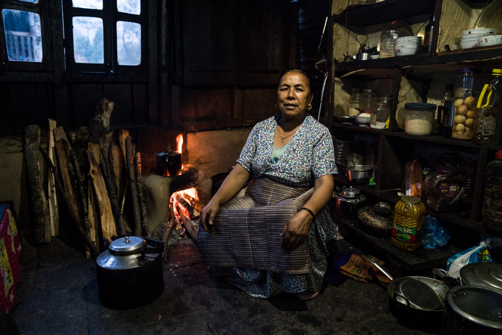 A woman in her kitchen poses for a portrait while cooking dinner.
