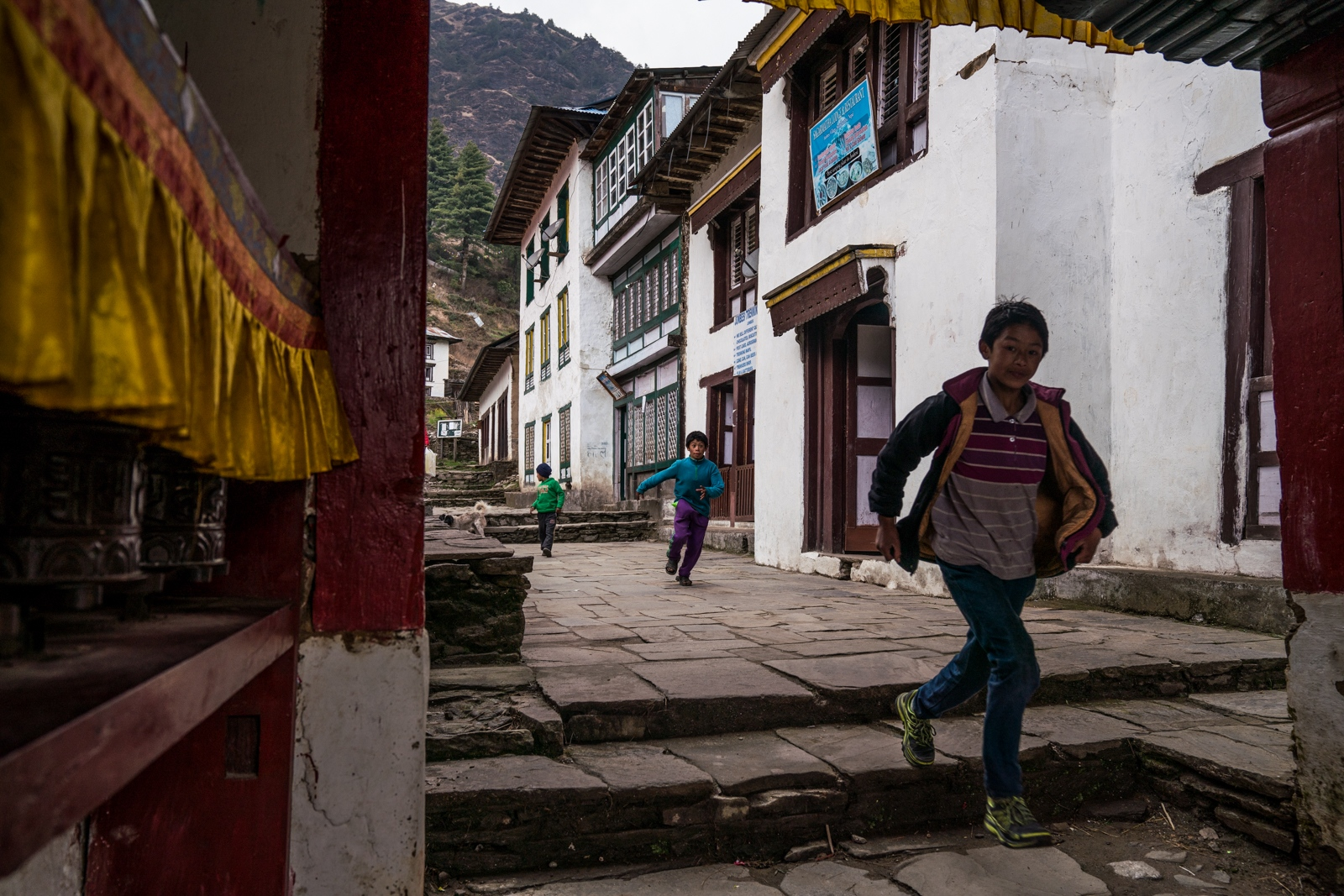 Children run through the streets of Junbesi in the Himalayan foothills.