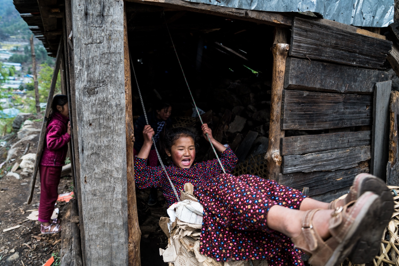 Children play on a makeshift swing inside a wood storage barn.