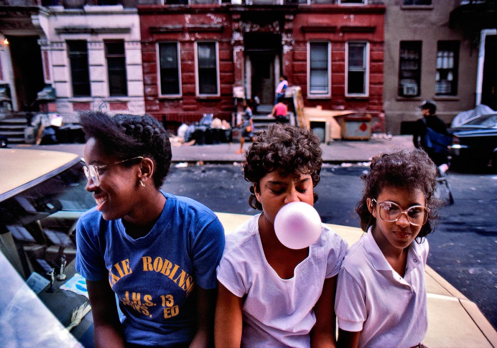 Schoolgirls sitting on car bonnet, upper east side