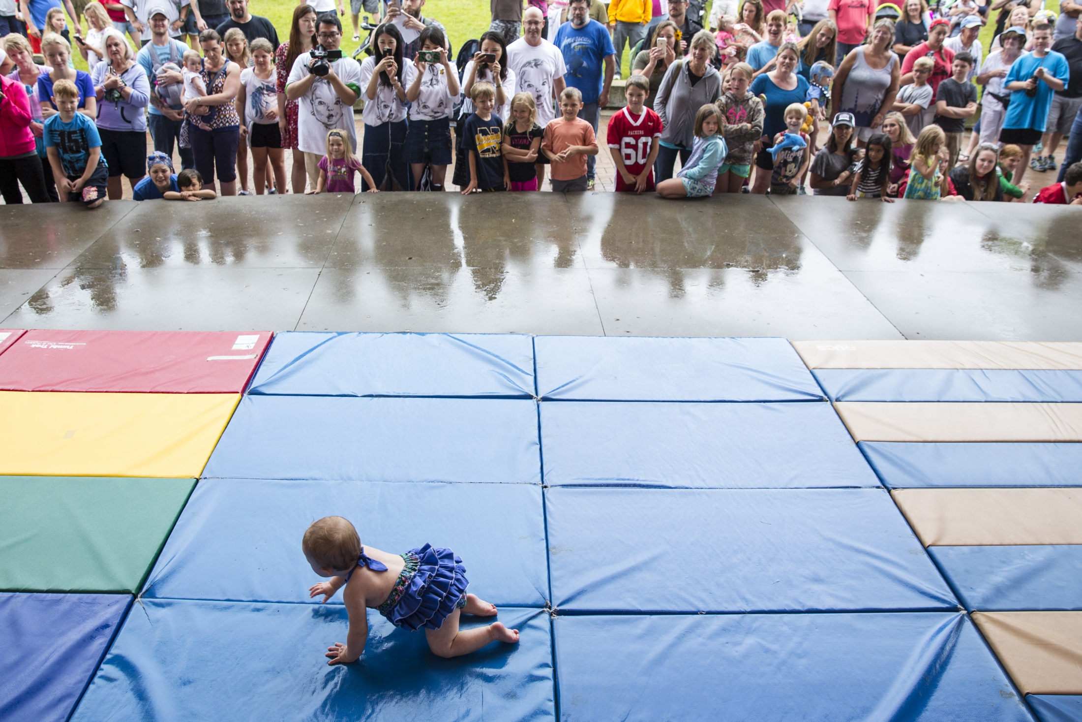 10-month-old Piper Nelson crawls across the mat during a baby crawl contest at National Baby Food Festival in downtown Fremont, Mich. on Saturday, July 22, 2017. Nelson finished her heat in first place.
