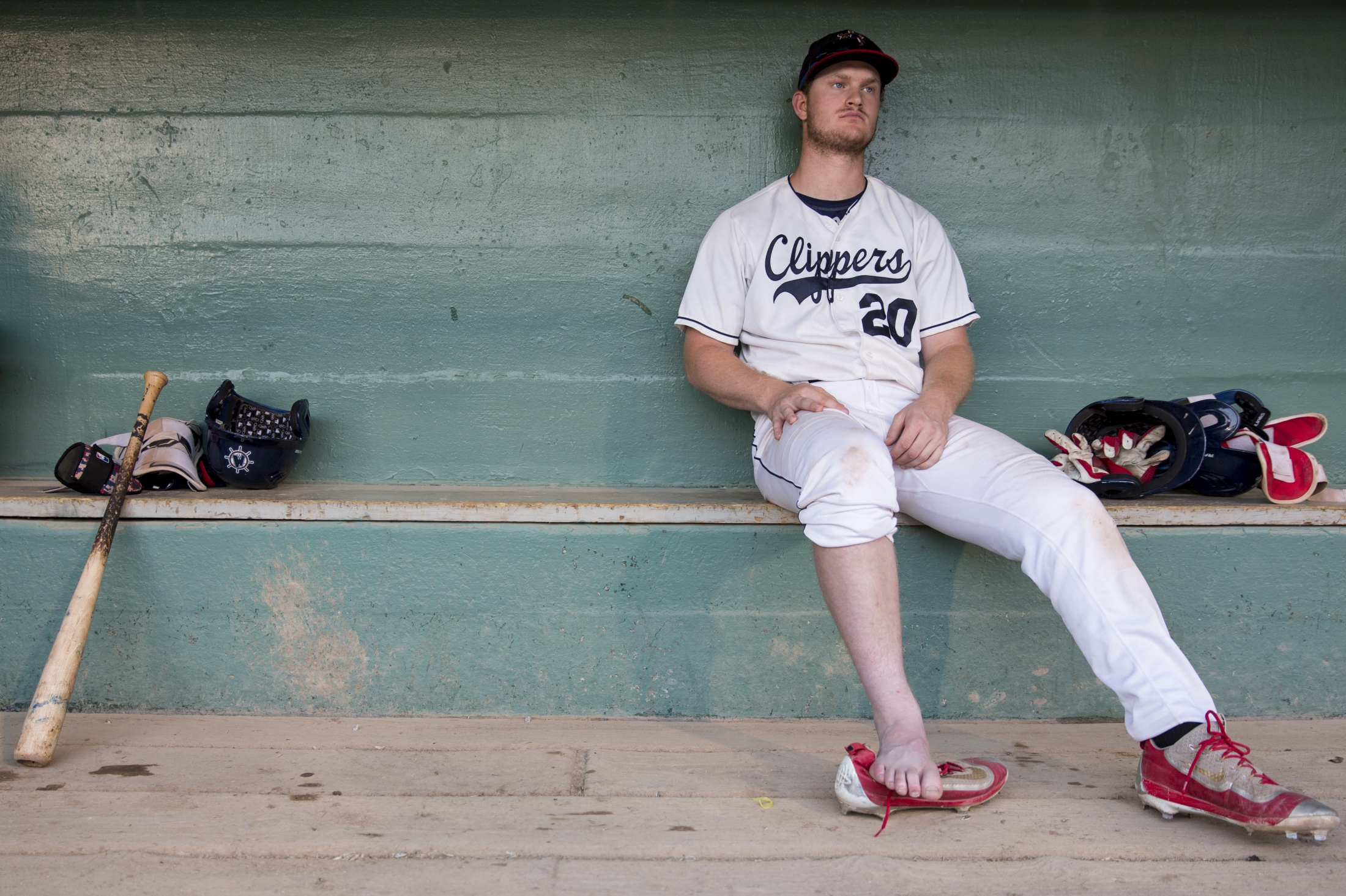 Muskegon Clippers Peter Zimmermann (20) rests in the dugout after an ankle injury on the right foot during a game against Grand River Loggers at Marsh Field in Muskegon on July 6, 2017. Zimmermann said he was disappointed especially because his family traveled a long way from Missouri to watch the game. Loggers defeated Clippers 6-2.