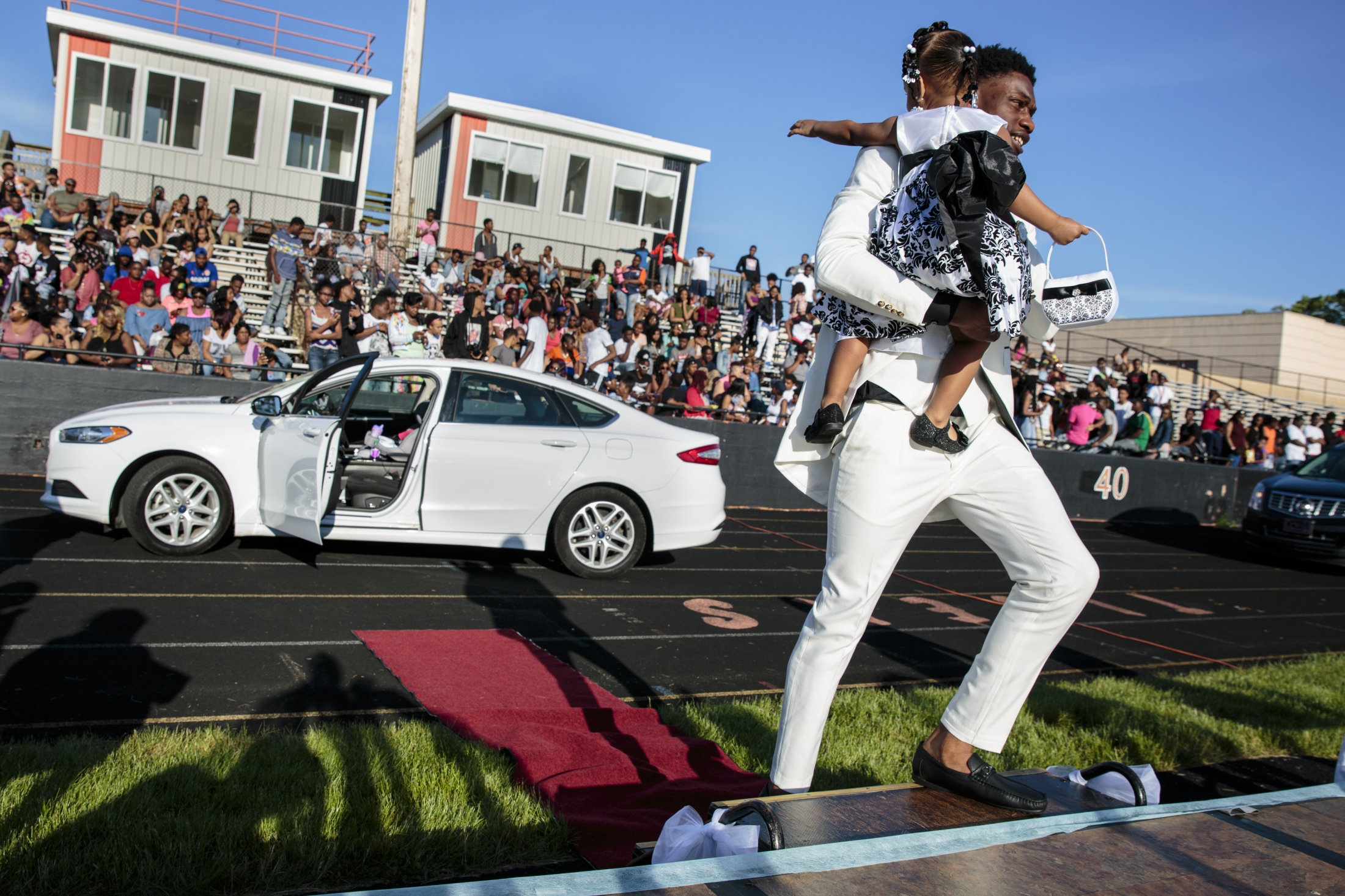 Javonte Kendrick carries his niece Monyae Helms, 1, to the stage as their names were announced during Muskegon Heights Academy's traditional pre-prom Showoff in Muskegon Heights, Mich. on May 27, 2017. A longstanding tradition, Showoff involved 40 students and their dates driving up in front of a platform on the high school football field before heading to the prom.