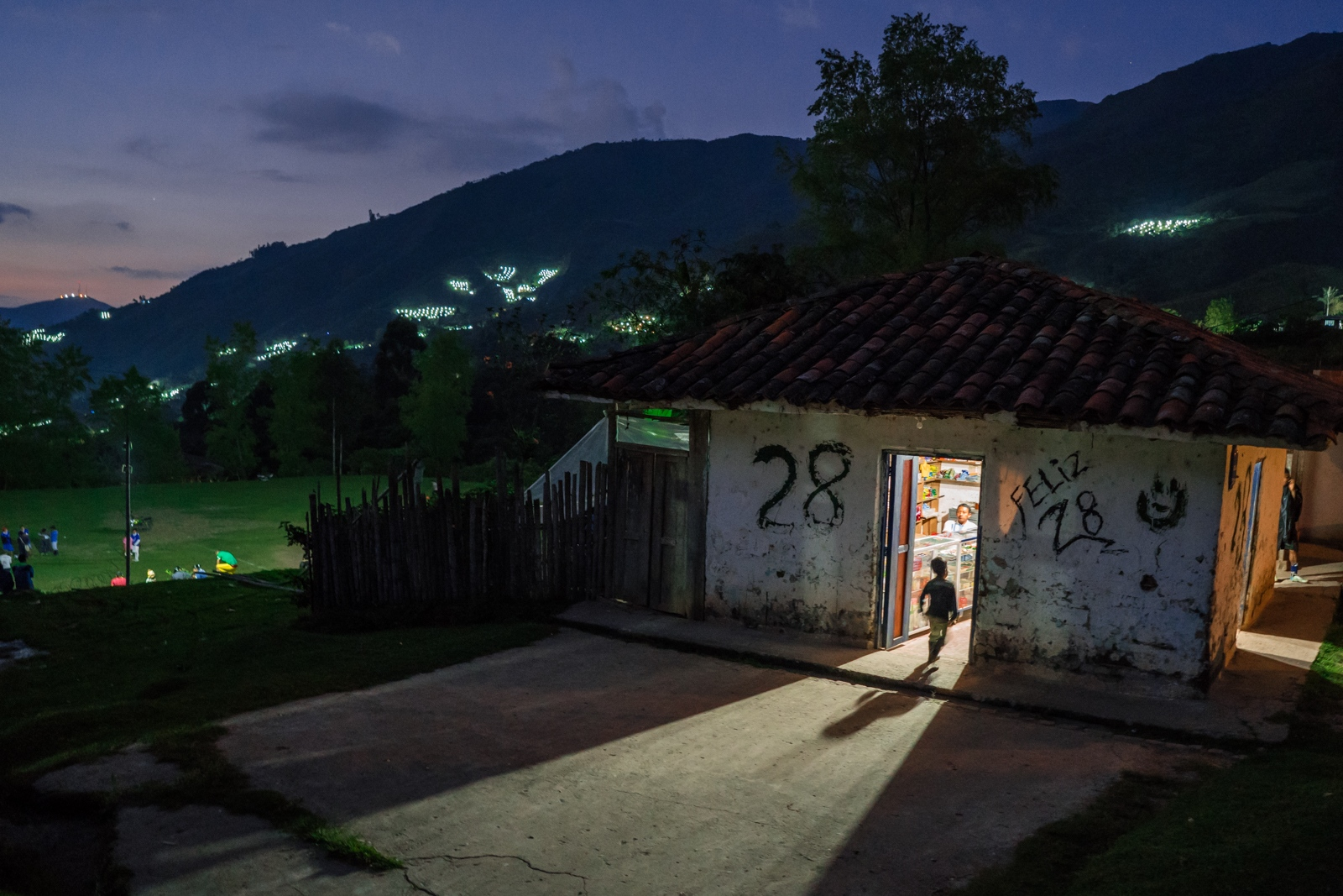 A kid walks into a shop in the north of Cauca-Colombia, around him mountains with marijuana fields start to be lighten up for the night.